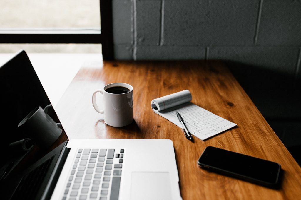 Picture of a work desk by Andrew Neel on Unsplash. Laptop, coffee mug, cell phone and notepad.