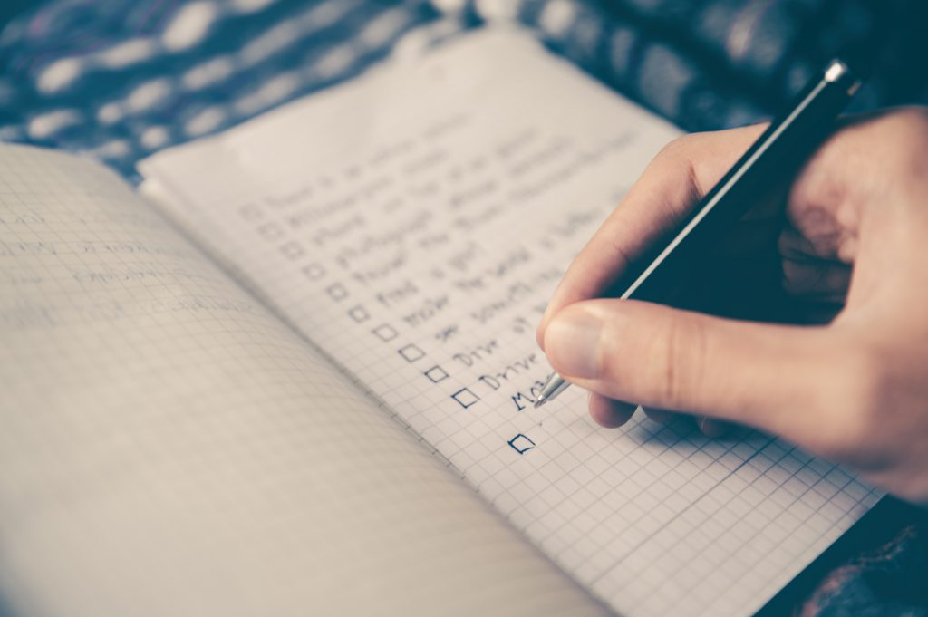 Picture of a mans hands writing a list.