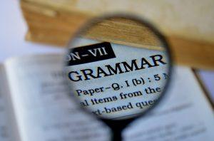 "Magnifying glass examining the word ""grammar."""
