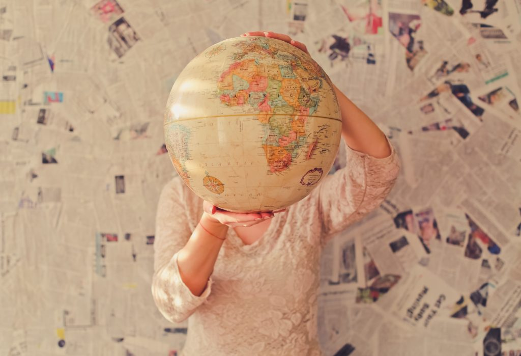 Woman holding globe in front of face; travel; travel writing