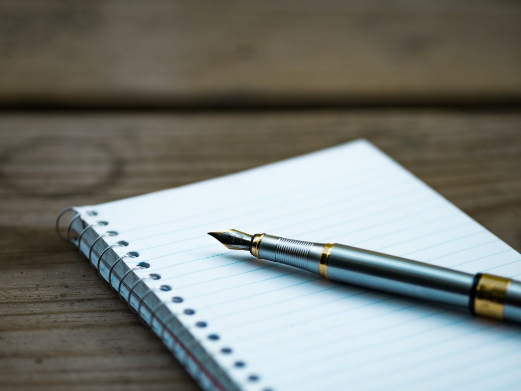 pen and notebook how to start a writing careerPhoto by Aaron Burden on Unsplash