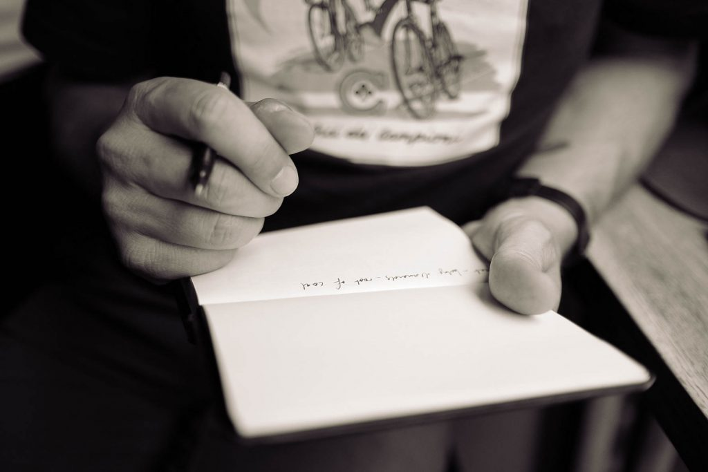 man writing in notebook Photo by Calum MacAulay on Unsplash