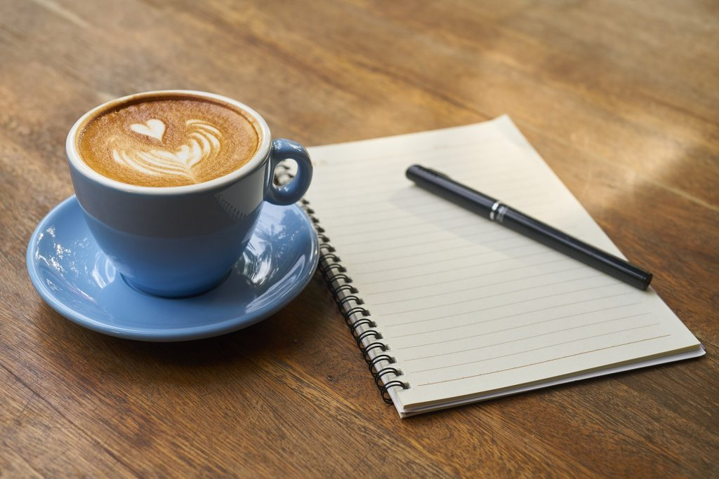 Coffee, notebook, and pen; book recommendations
