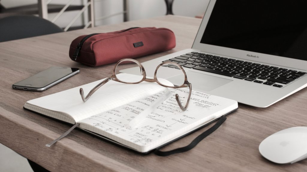 research; glasses, notebook and laptop Photo by Dan Dimmock on Unsplash