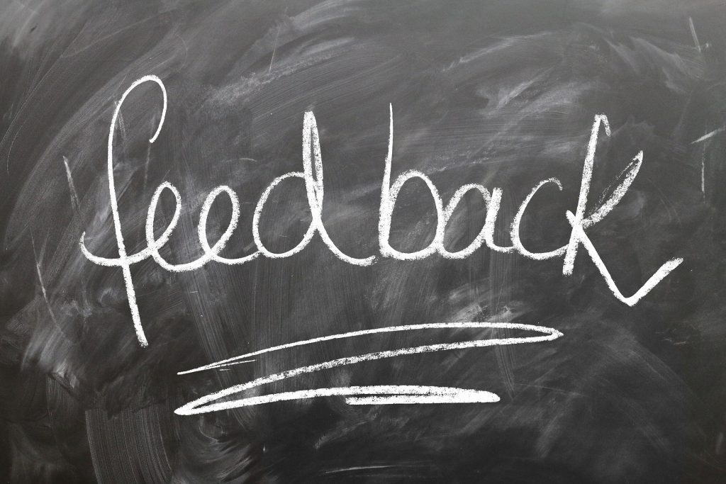 feedback written on chalkboard; ask for feedback when you're a freelance writer, to under-promise and over-deliver.
