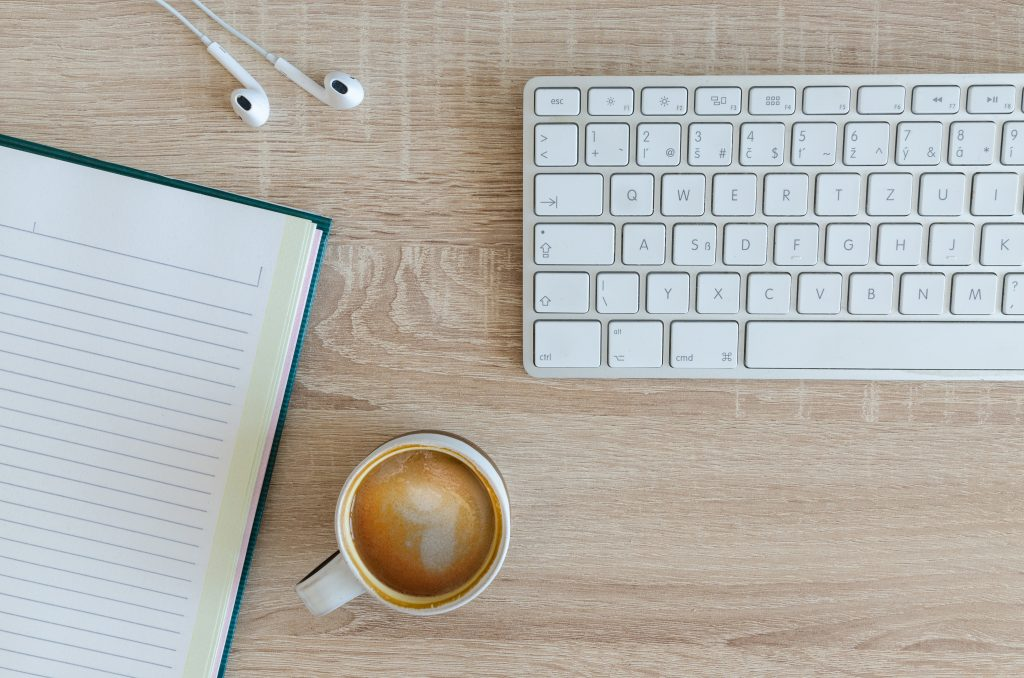 writing keyboard notebook earphones mug Photo by Lukas Blazek on Unsplash