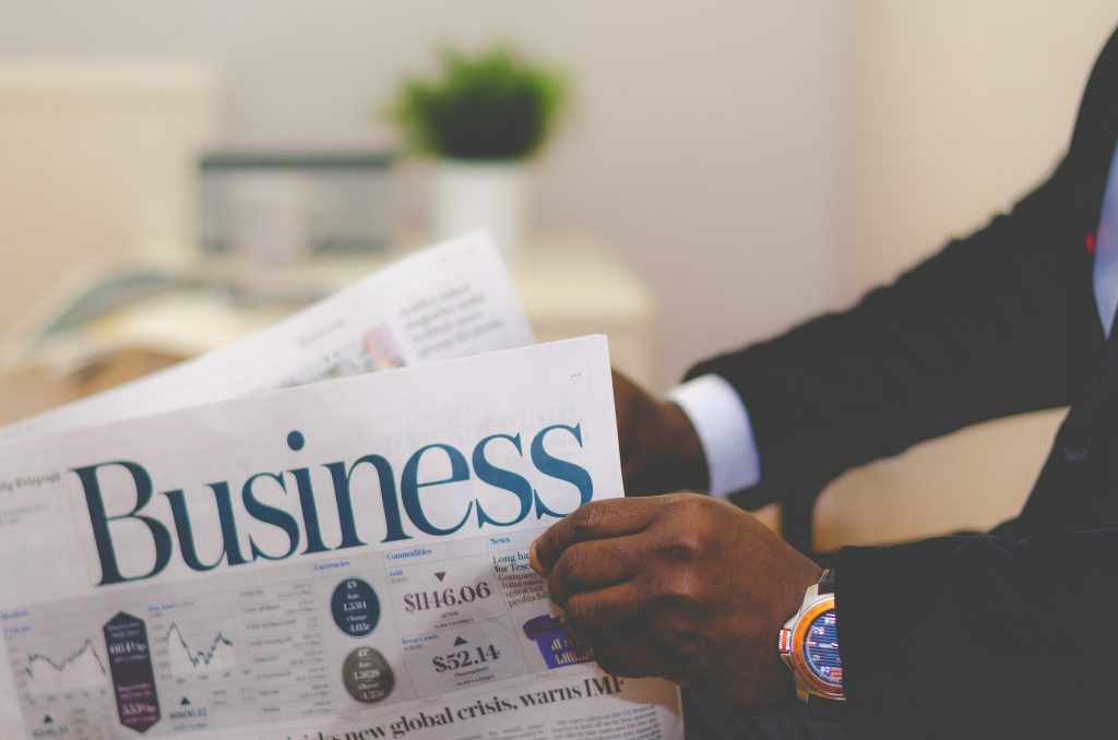 hands holding business section of newspaper; business books; Photo by Olu Eletu on Unsplash