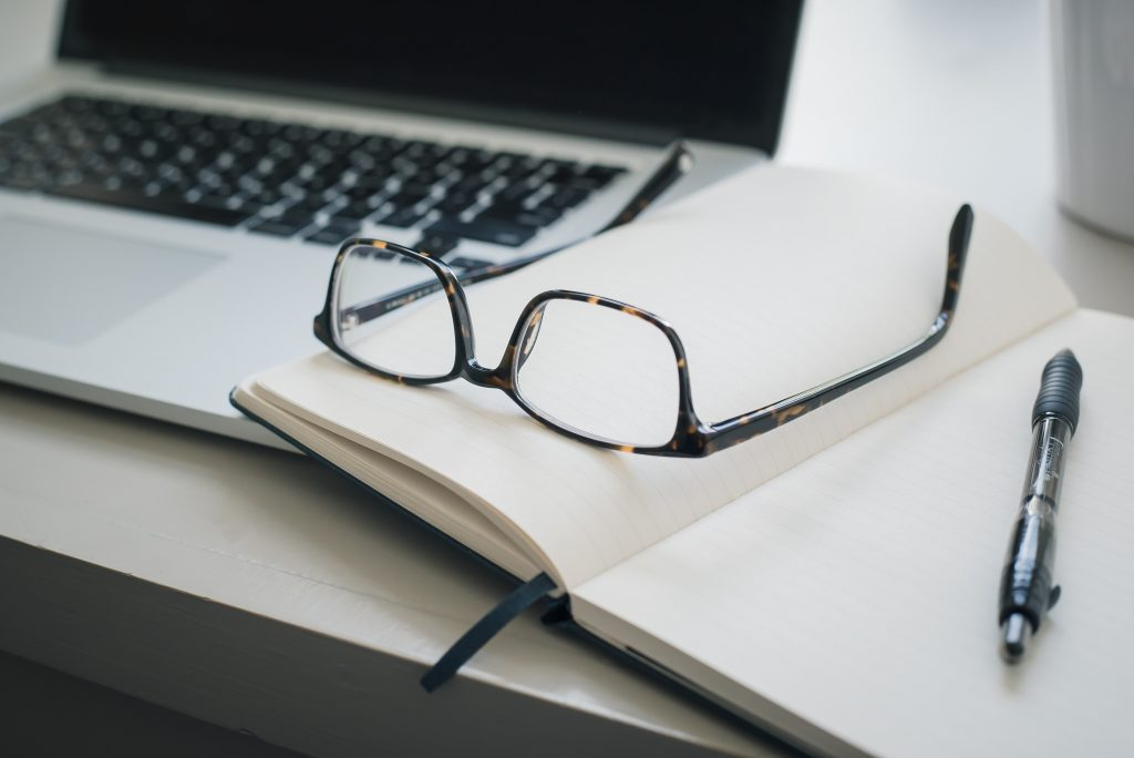 get paid for your writing; desk with notebook, glasses and laptop Photo by Trent Erwin on Unsplash