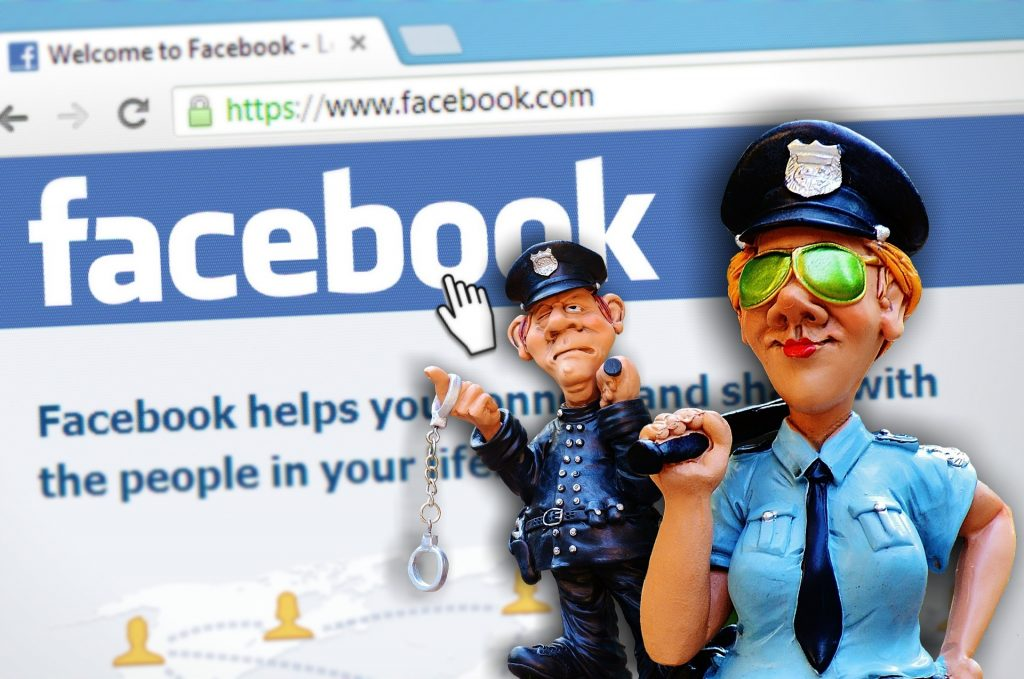 Computer screen showing Facebook with two clay police officers in front; follow Facebook group rules