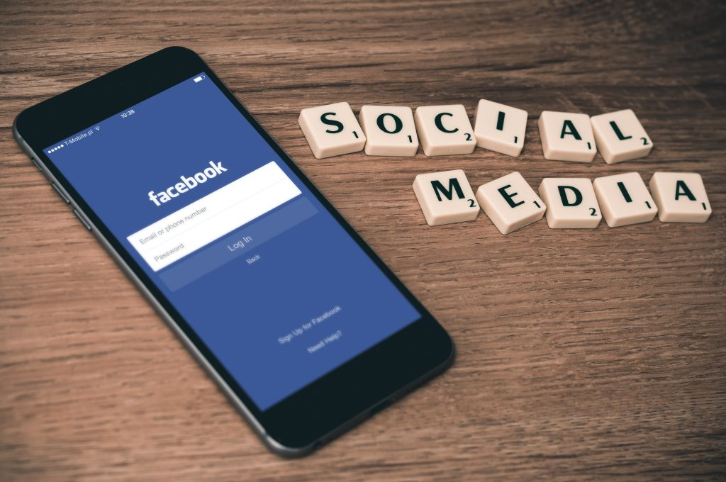 "cell phone with facebook screen and ""social media"" spelled out in tile letters Photo by William Iven on Unsplash"