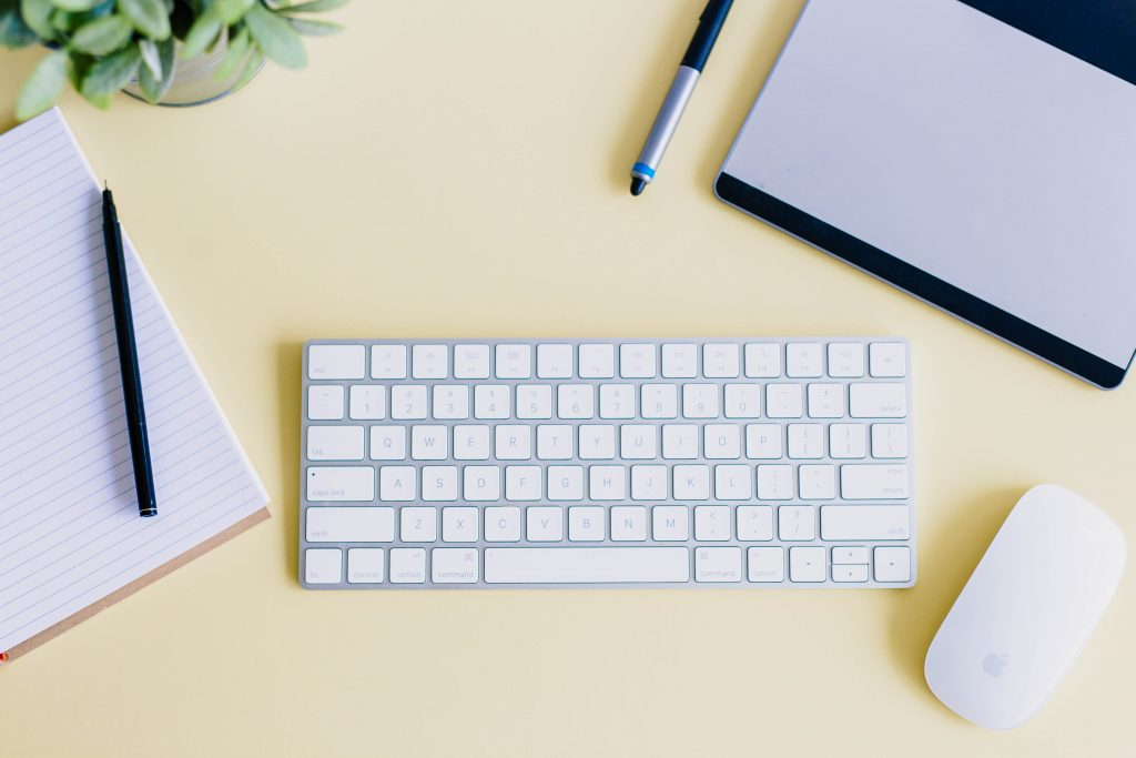 Picture or organized desk with keyboard, notebook, and pen. Project Management for Freelancers Photo by Amy Hirschi on Unsplash