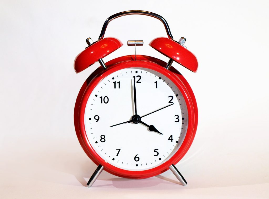 red alarm clock showing 4:00 o'clock