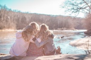 Mother and daughters outdoors, hugging. Photo by Courtney Prather on Unsplash