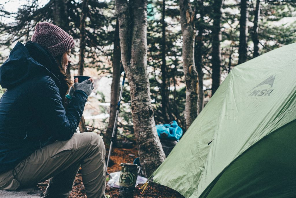 Woman drinking coffee by a tent; camping, Photo by Julian Bialowas on Unsplash