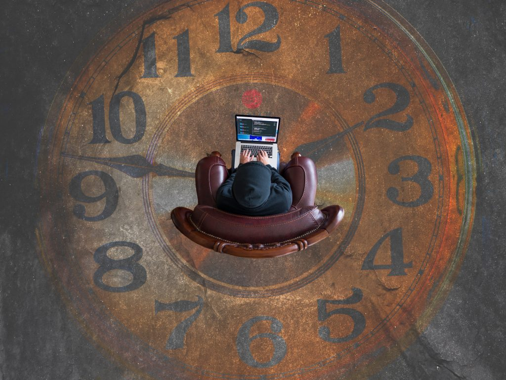 Person working on laptop; picture taken from above and showing a floor clock. Time Panther time tracking software; Photo by Kevin on Unsplash
