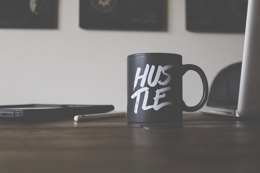 hustle mug on a writer's desk