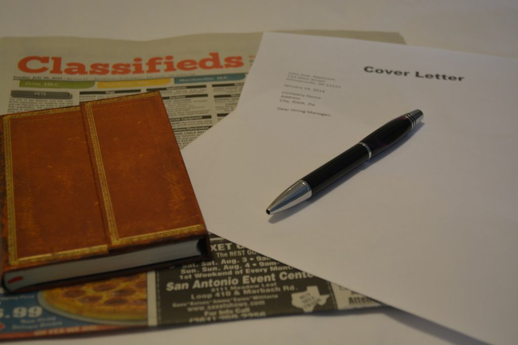 Writing resumes for pay: cover letter, notebook, pen and classifieds
