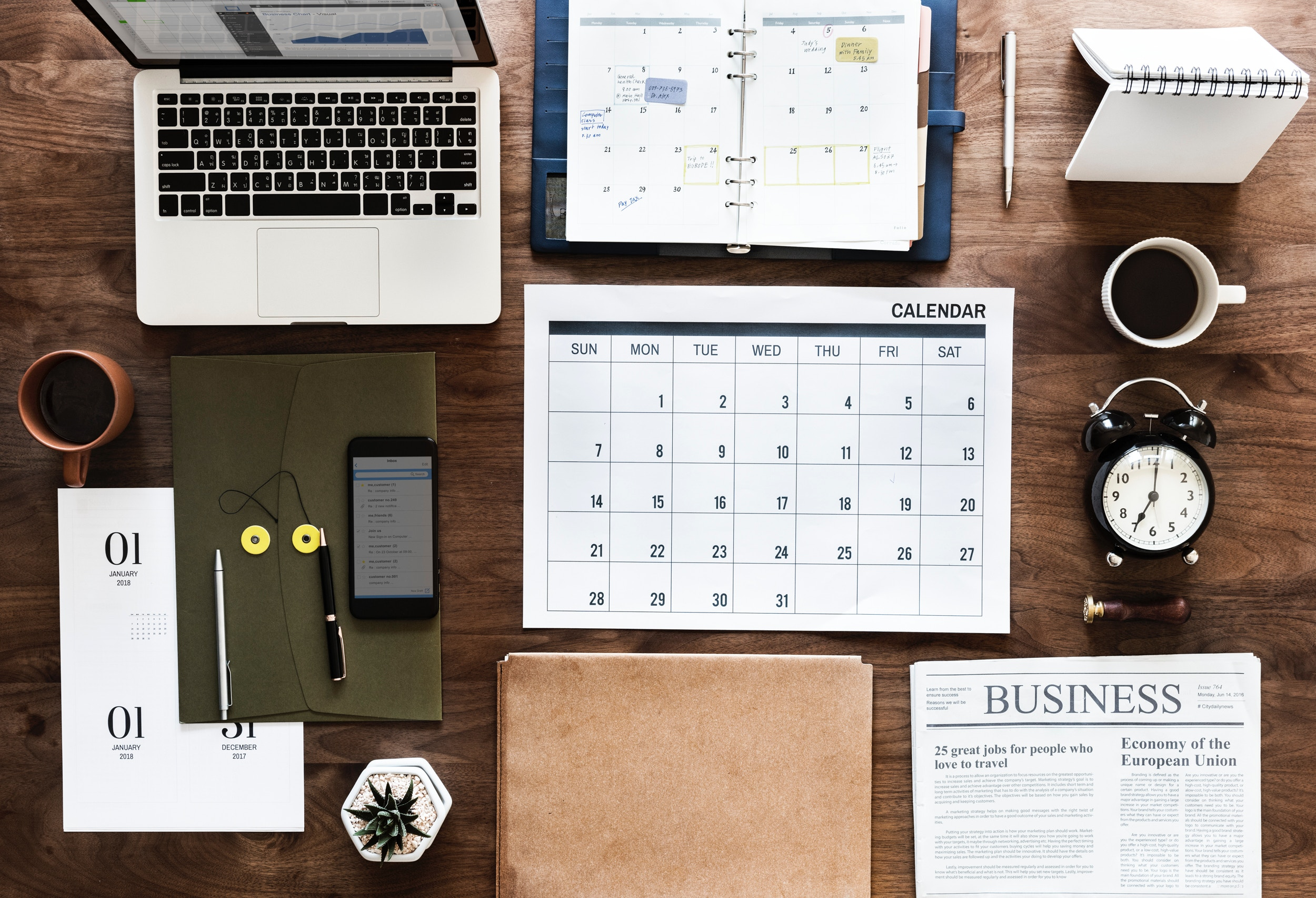 Where to find freelance writing gigs, part 3: warm pitching, MultiTalented Writers. Well organized desk with laptop, planner, calendar, cell phone, plant, a folder, a clock, and a newspaper turned to the business section. Photo by rawpixel on Unsplash