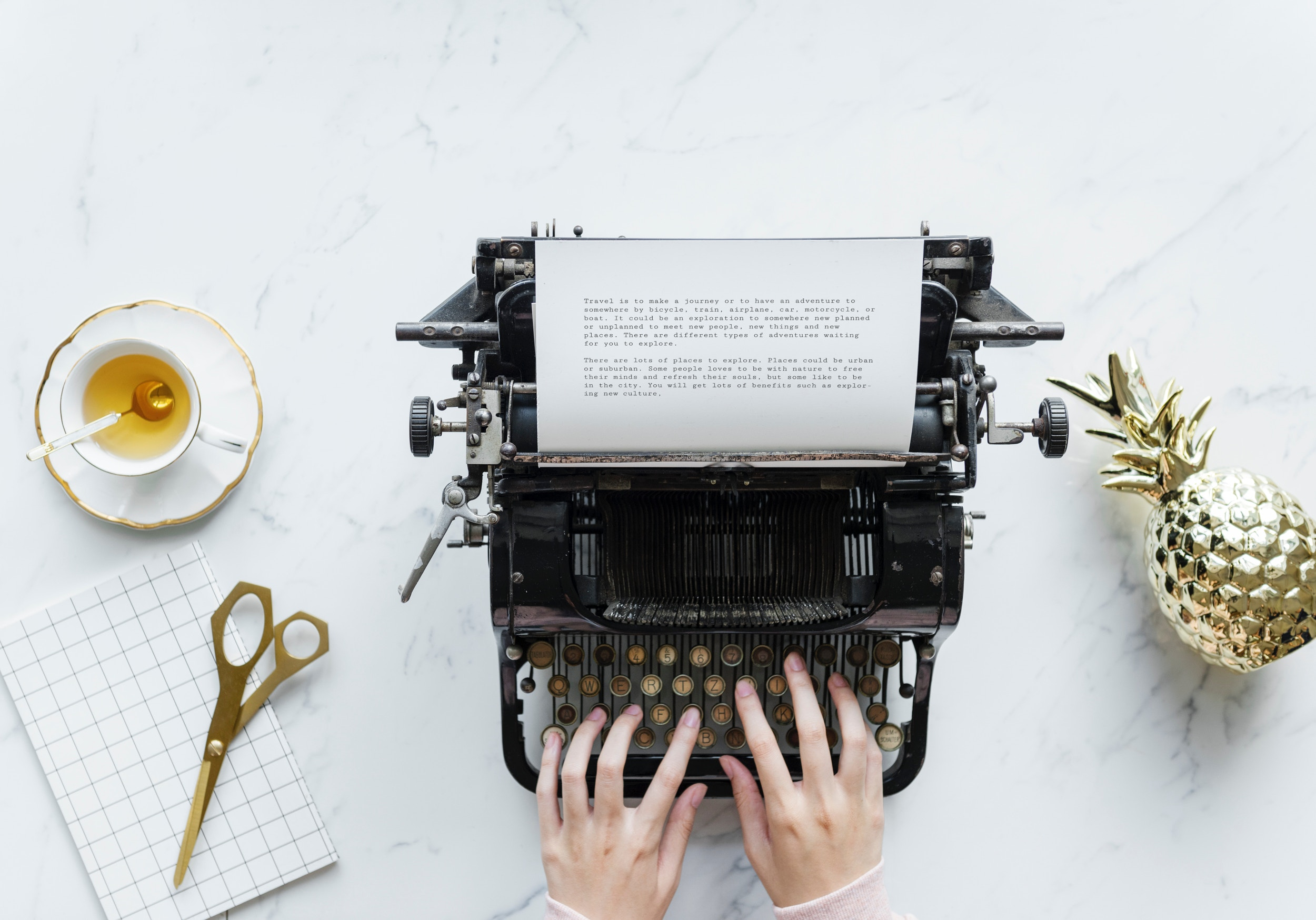 Woman's hands typing on a typewriter. Desk contains a pair of scissors to the left and a golden metal pineapple to the right. Photo by rawpixel on Unsplash