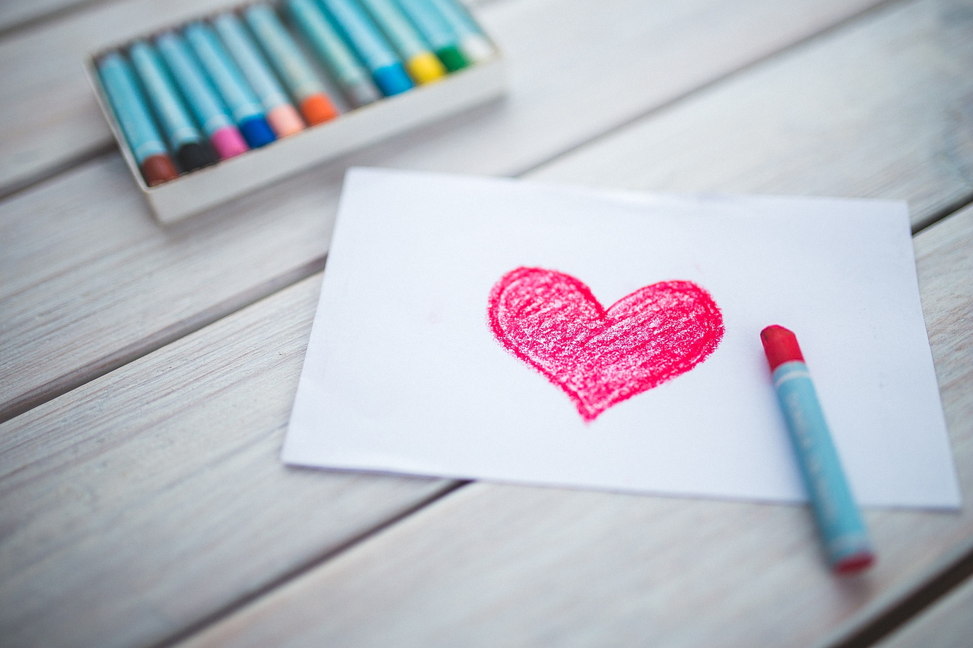 Get paid to write greeting cards: picture of a heart drawn in red crayon, with a box of crayons in the background, www.multitalentedwriers.com
