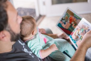 Parenting magazines and blogs that pay writers. Father reading to son, Photo by Picsea on Unsplash