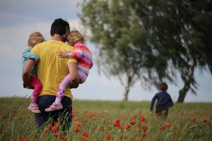 Photo of a family in a field of tall grass and red flowers. Seen from the back. The father is holding two children, one on each hip, and an older boy is running in front of them. Photo by Juliane Liebermann on Unsplash