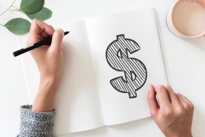 Female hands drawing money sign in a notebook. Photo by rawpixel on Unsplash