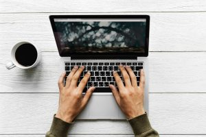 Male hands typing on a laptop,with a coffe cup sitting on the table to the left.