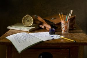 Antique desk with a notebook, ink, and ink pens, a cup full of pencils, a satchel, and a clock over a notebook. A notebook that has been written in with a fountain pen sits open on the desk.