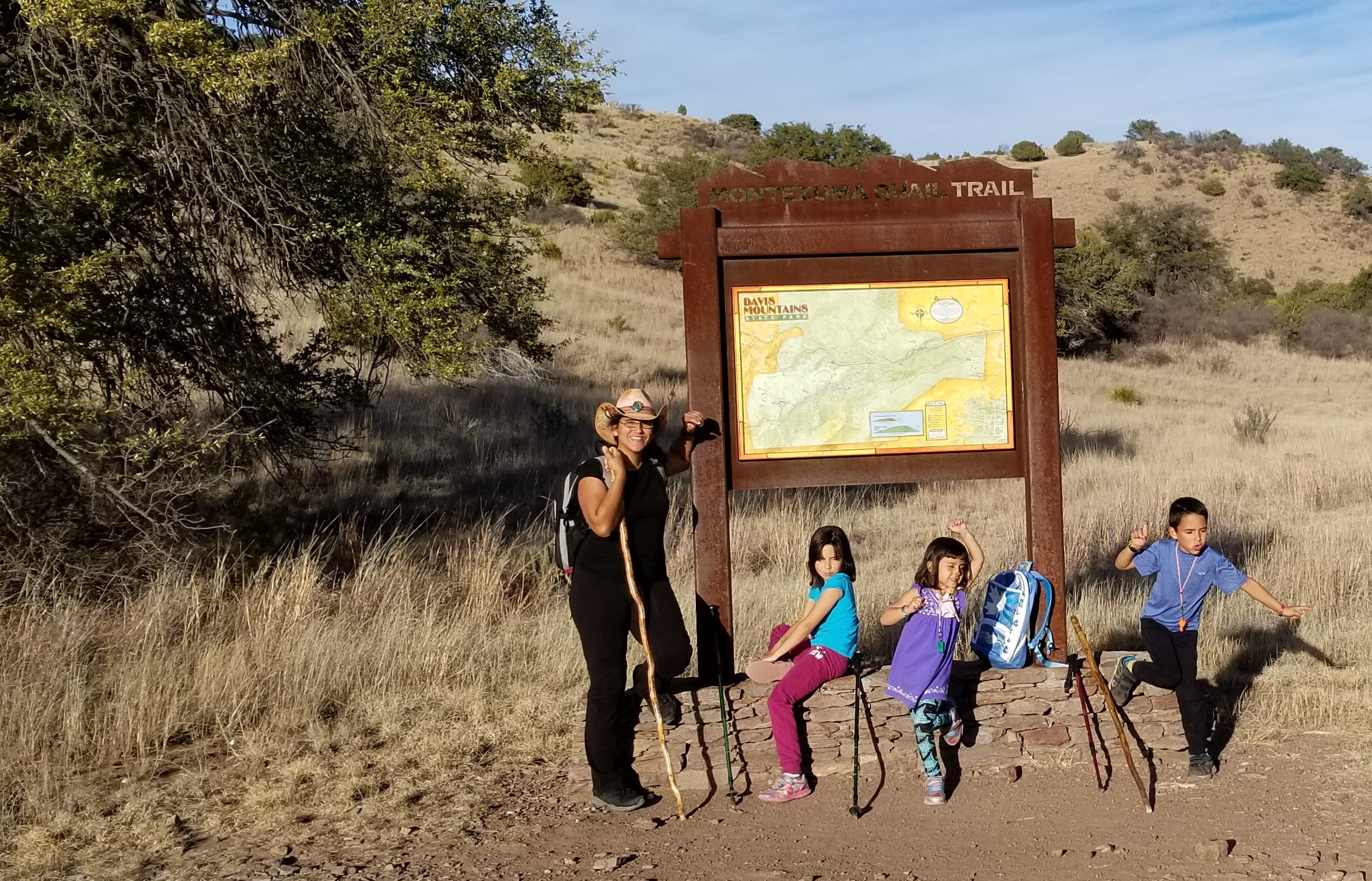 Mother, 9-year-old daughter, 4-year-old daughter, and 6-year-old son at a hiking trailhead sign.