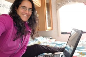 A woman has taken a selfie, smiling at the camera, with a laptop in front of her. She is sitting on a bed inside an RV. The window and a closet door can be seen in the background.
