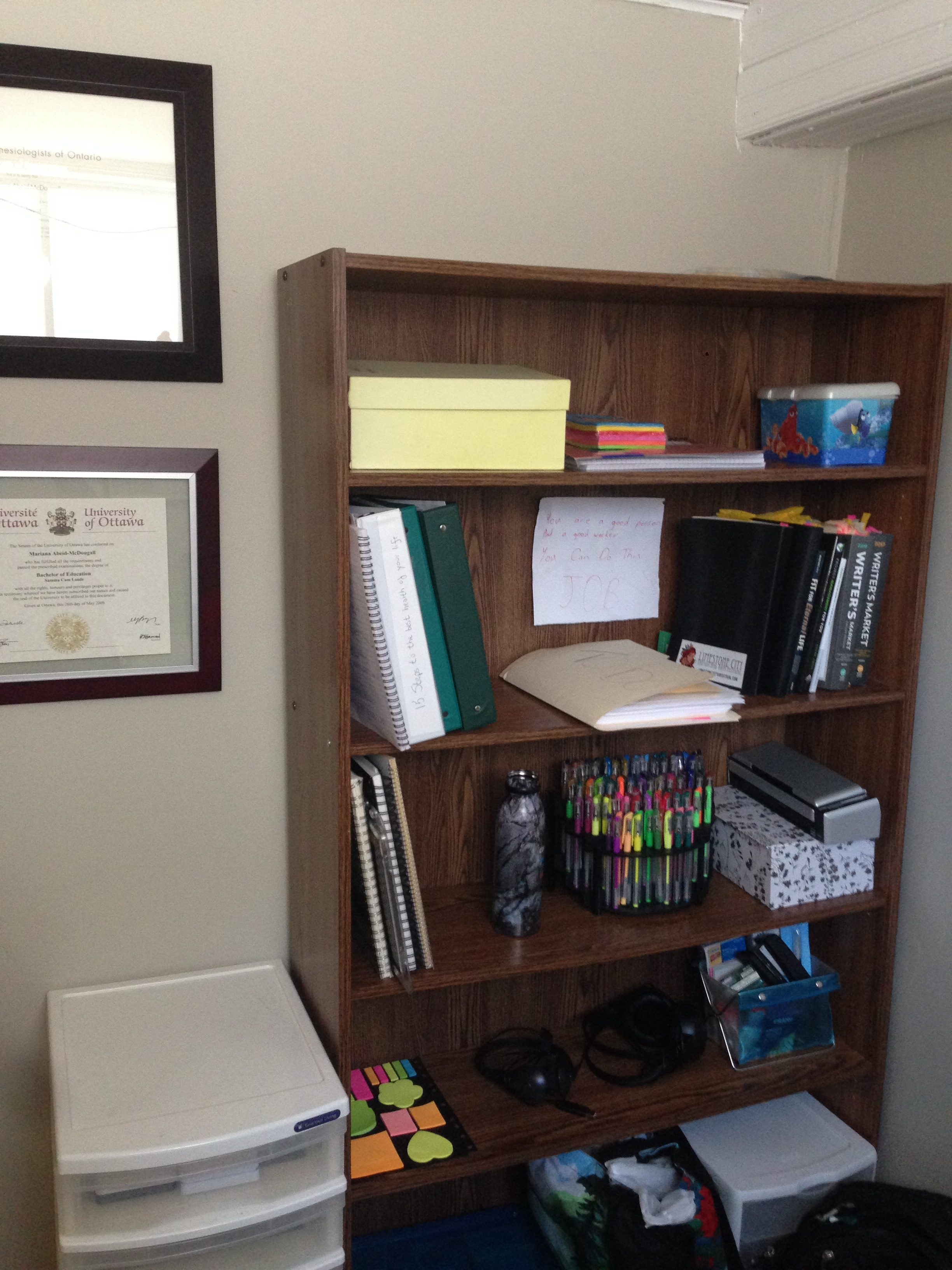 Work Spaces for Writers: A bookshelf with books, binders, decorative boxes, pens, and a water bottle. To the left of the bookshelf are framed degrees on the wall, and on the floor a plastic drawer tower.