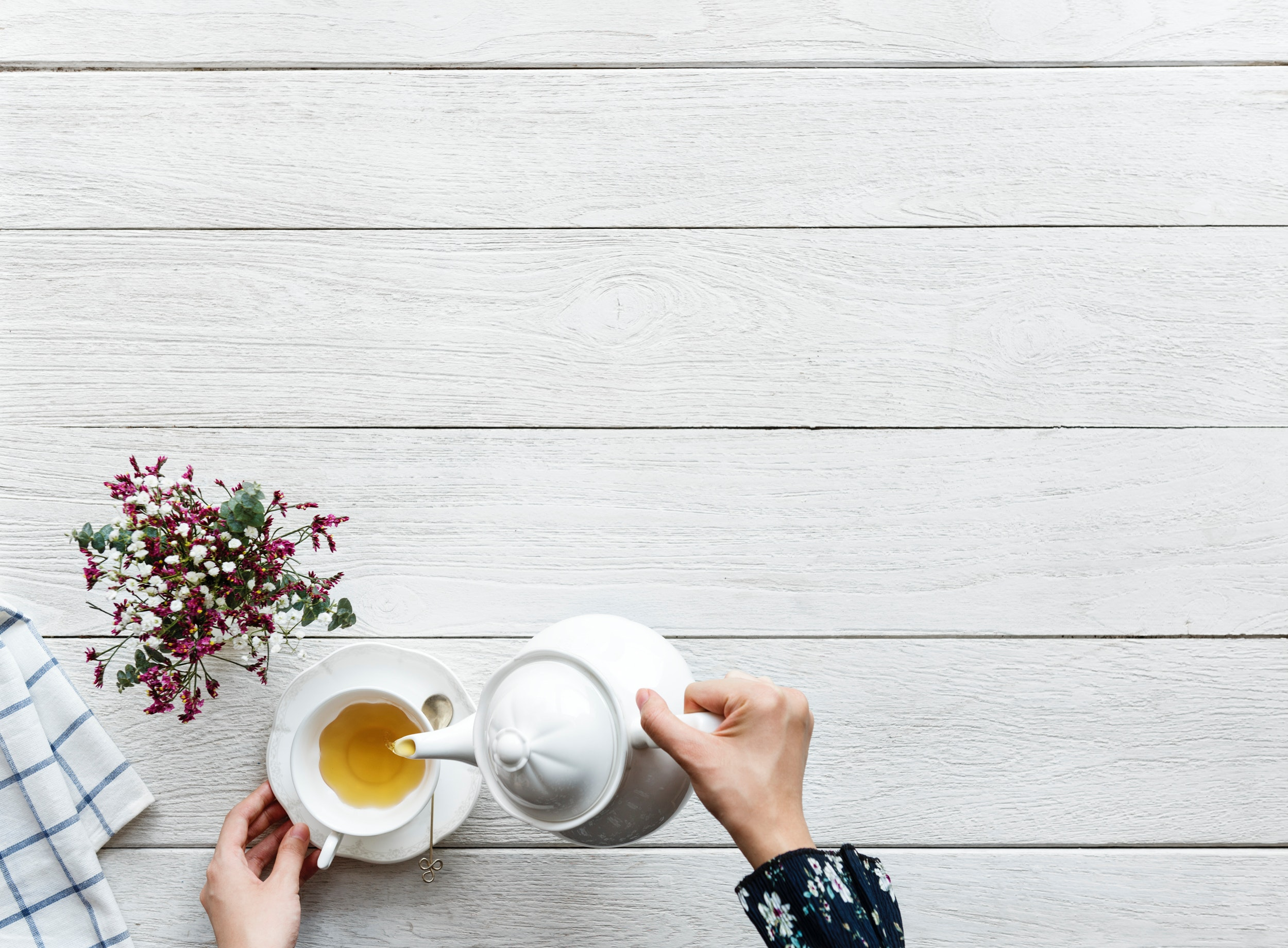 Self-care for writers: Hands pouring tea from a teapot into a teacup. flowers are to the left of the hands.