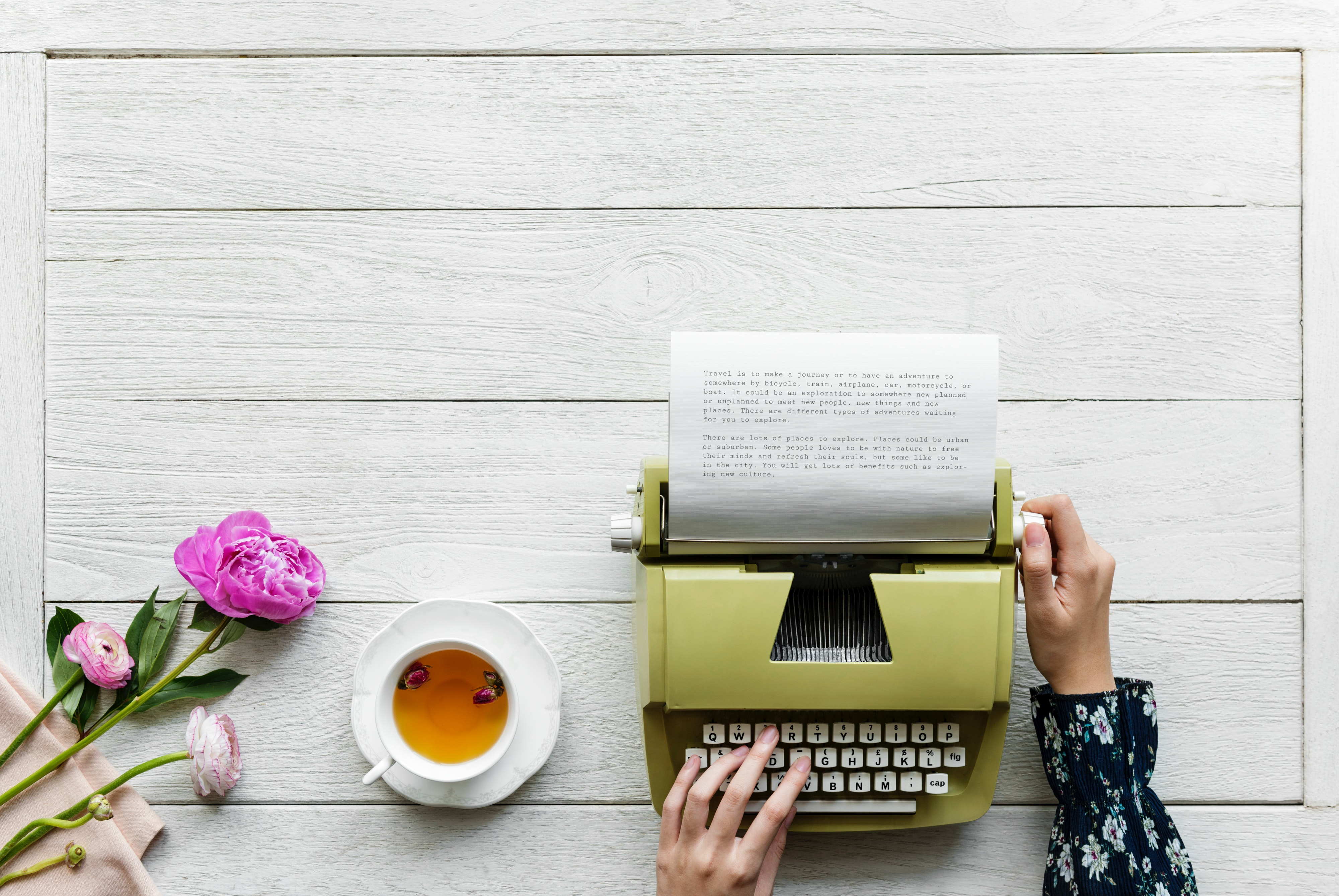 Picture of hands putting paper through a green typewriter. To the left is a cup of tea and some pink flowers. Photo by rawpixel.com from Pexels
