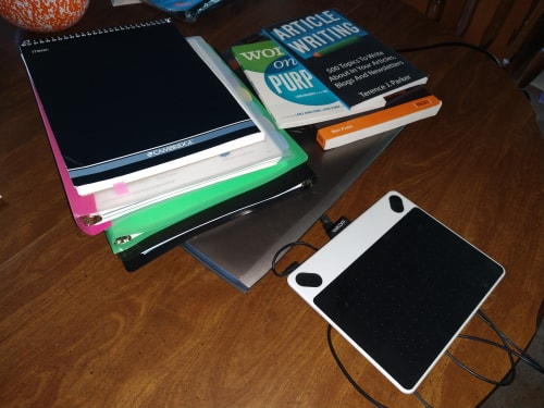 Office in a bag: A tablet, some notebooks, a laptop, and some books.