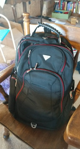 Work Spaces for writers: the office in a bag. Picture of a black backpack with red trimming.