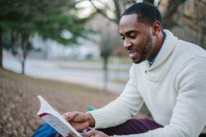 Man smiling while reading a book. Photo by nappy from Pexels