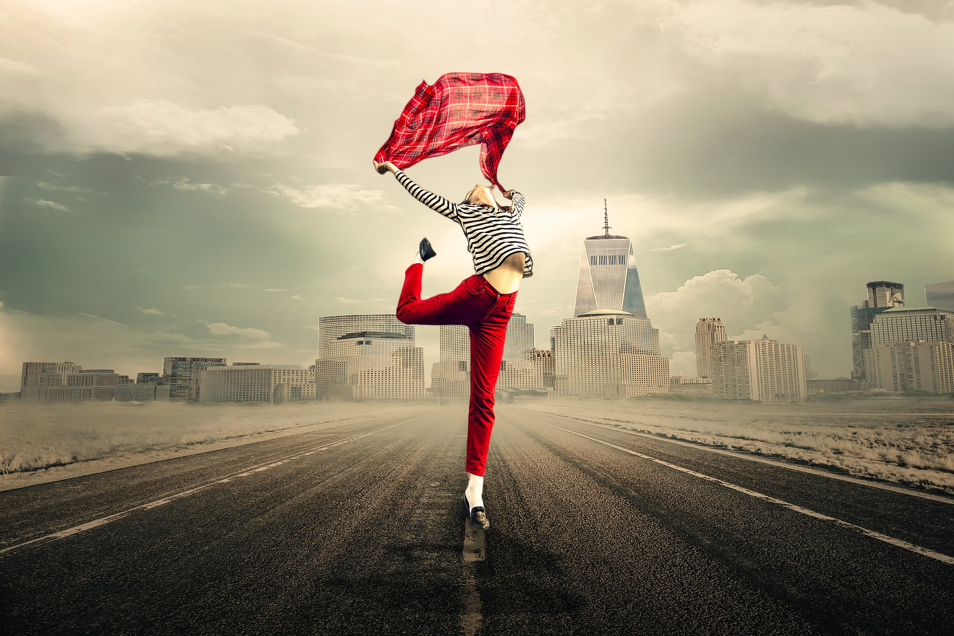 girl in red pants and striped black and white top holding a red scarf above her head and doing a ballet move. She is on a road, with buildings in the distance.