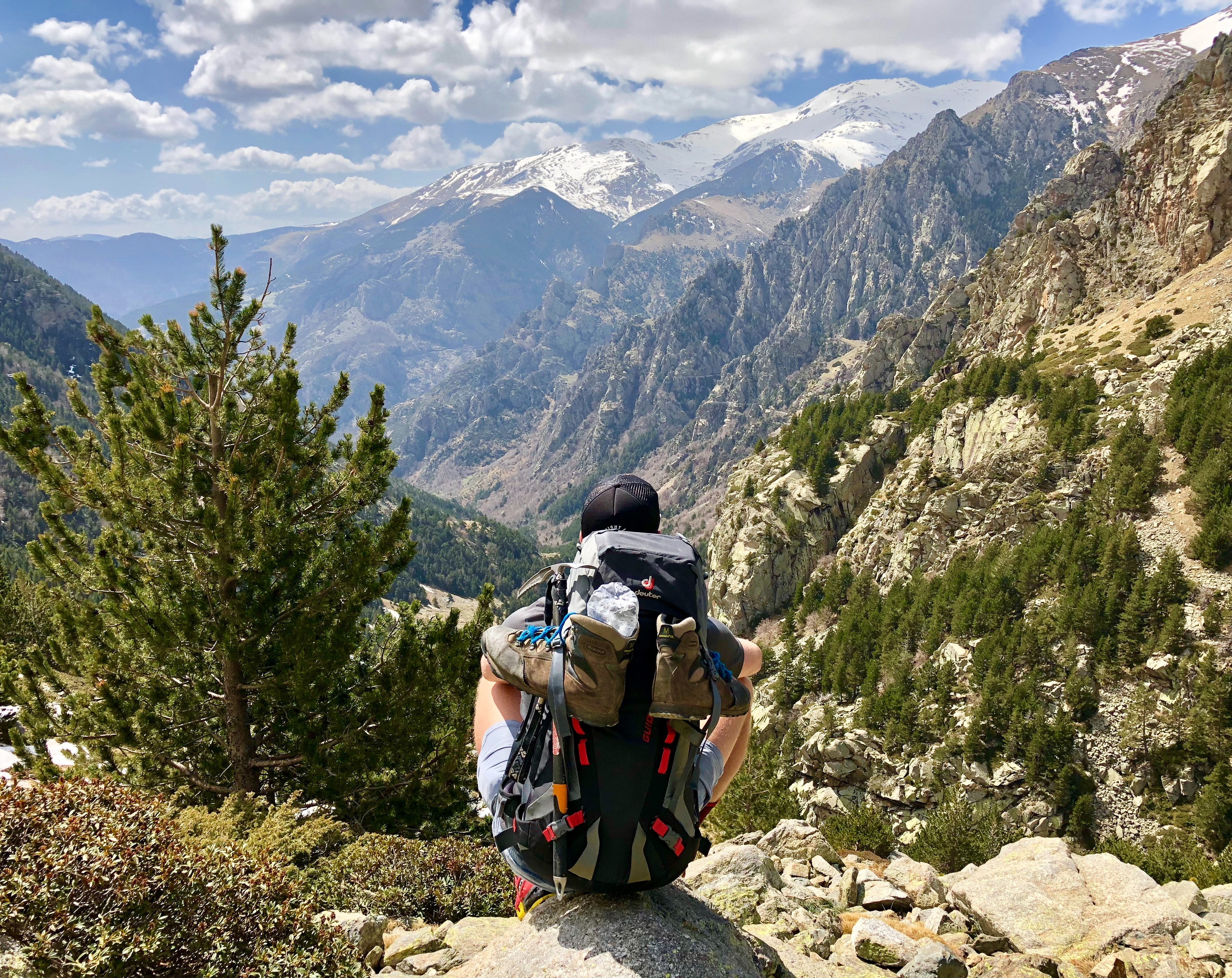 Photo by Marc Rafanell Lopez on Unsplash. Person sitting on a rock looking at mountains. the person is wearing a touque (wool hat) and a hiking pack. In front of the person are several mountains and pine trees.