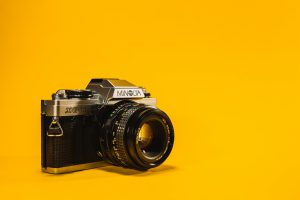 vintage camera against bright yellow background. Photo by Paul Gaudriault on Unsplash