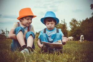 Two boys wearing hats sitting on the grass and reading a book together. Get paid to write for children. Photo by Victoria Borodinova from Pexels