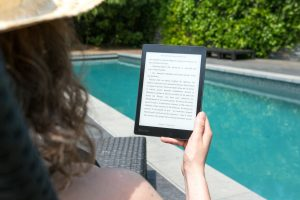 Person with long curly hair holding an eReader in front of a pool. Photo by Perfecto Capucine from Pexels