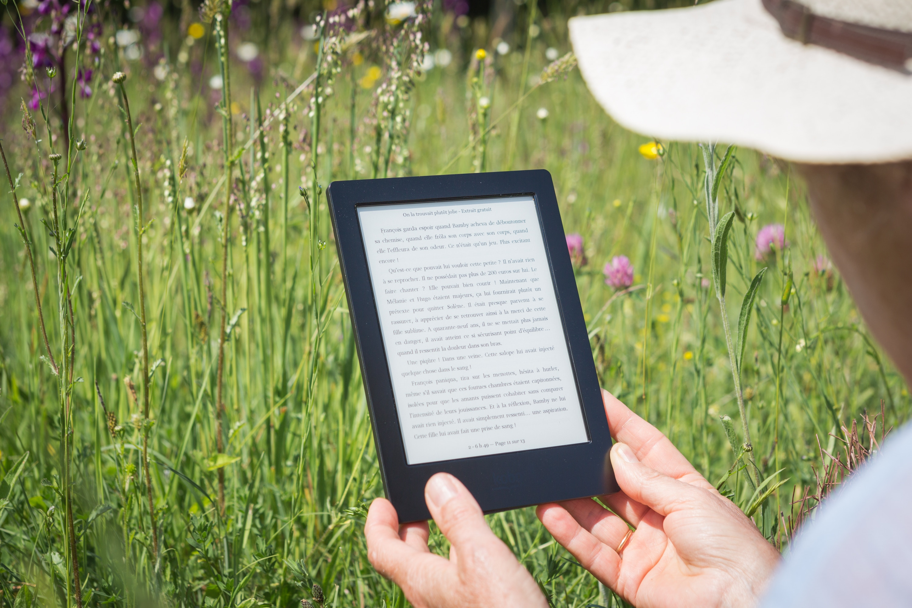 Person wearing a hat holding an eReader in a grassy field, Photo by Perfecto Capucine on Unsplash
