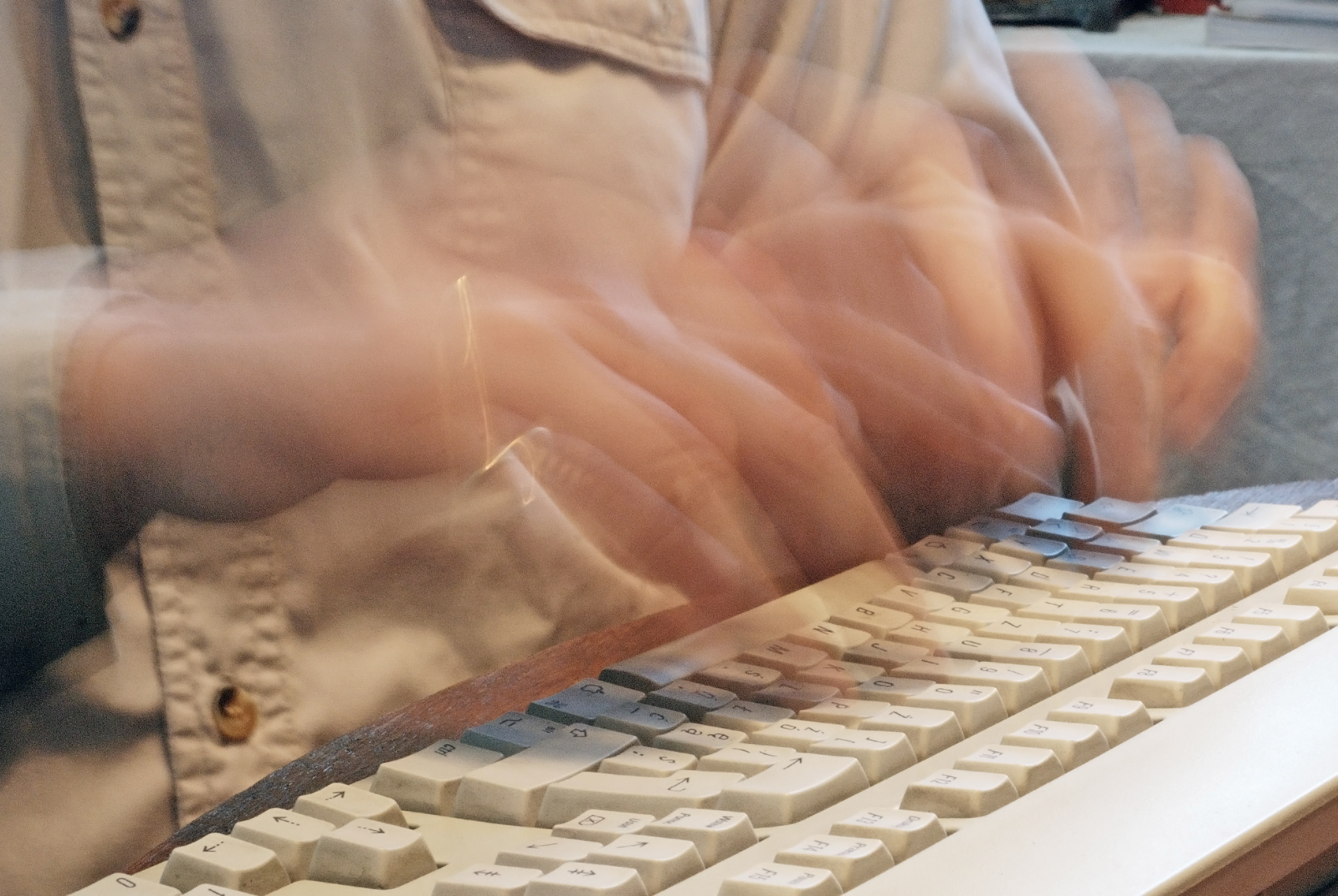 fast writer. Photo of hands on a keyboard showing movement effect