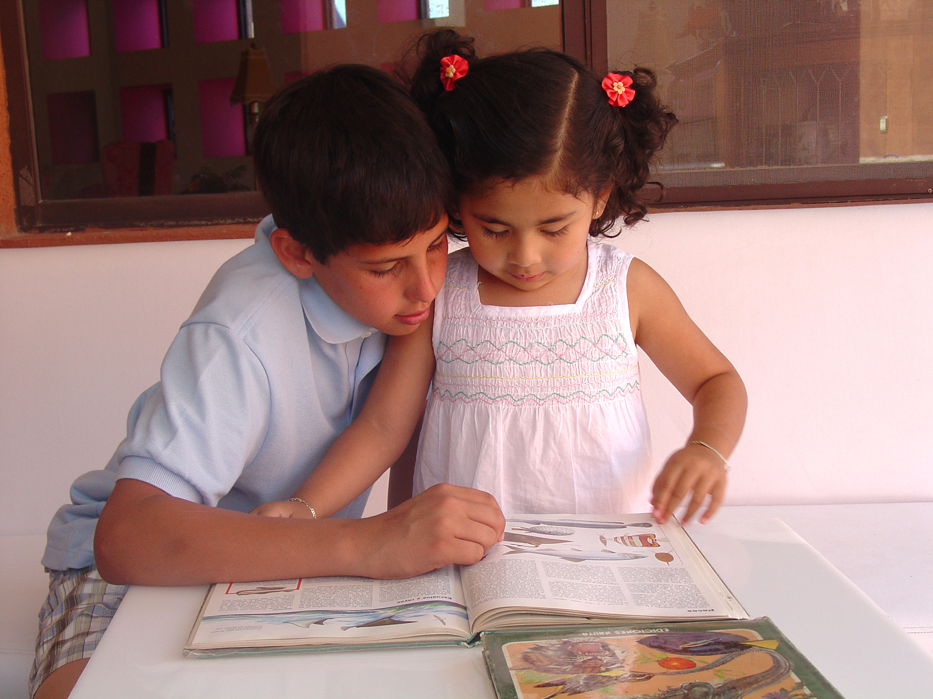 A boy showing a girl something in a book.
