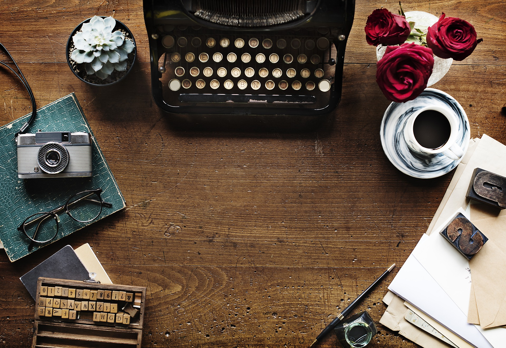 Typewriter with roses, mug, and books on a table