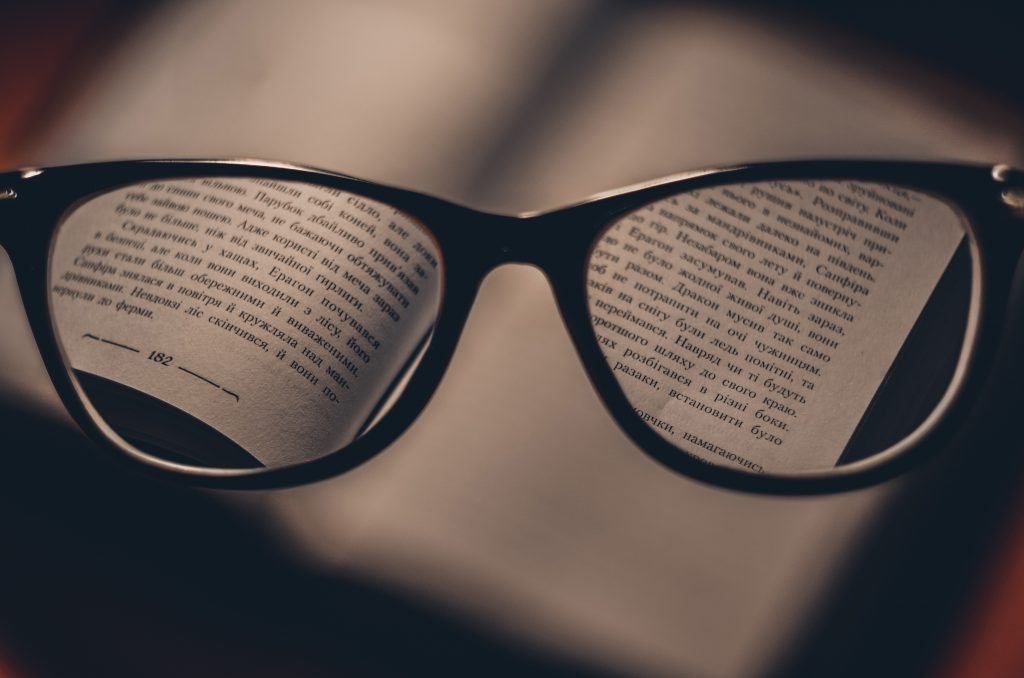 words on a book seen through the lenses of a pair of glasses. Photo by Dmitry Ratushny on Unsplash