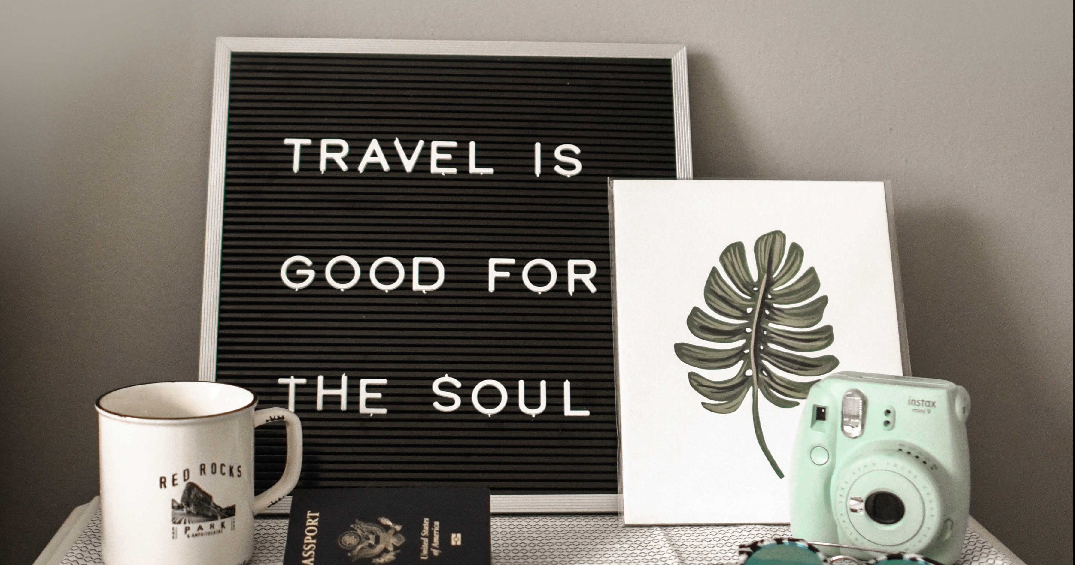 "Desk with a letter board saying ""travel is good for the soul."" On the desk are also a mug, a camera, and a picture of a palm leaf. Photo by Element5 Digital on Unsplash"