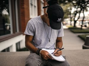 man wearing a baseball cap writing in a notebook. Photo by Brad Neathery on Unsplash