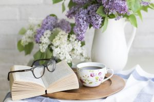 coffee, fllowers, book and glasses on a table